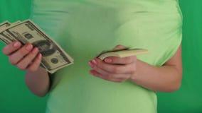 En un fondo verde considera dólares Las manos femeninas consideran d?lares en un fondo blanco almacen de video