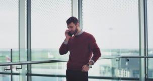 En un oficinista apuesto del hombre joven del centro de negocios moderno tenga una conversación sobre su smartphone metrajes
