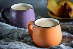En un pequeño café anaranjado de la taza con leche Después una taza púrpura y una magdalena en la falta de definición Fotos de archivo libres de regalías