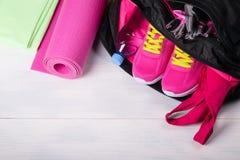 En un piso de madera se abren los deportes empaquetan con cosas rosadas en él imagen de archivo