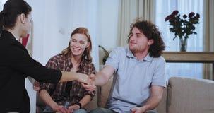 En un primer moderno de la casa en el agente inmobiliario atractivo de la mujer del sofá feliz haga un contrato para un par emoci almacen de metraje de vídeo