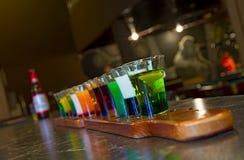 En un soporte de la tabla de billar con los vidrios coloreados de alcohol imagenes de archivo