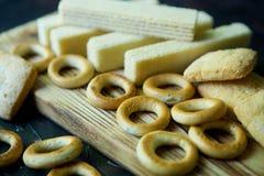 En un tablero de madera son los panecillos, las galletas y las galletas Imagen de archivo libre de regalías