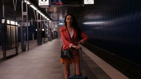 En un viaje de negocios - mujer con una maleta que espera impacientemente su tren almacen de video