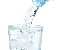 En un vidrio con el agua potable que fluye del hielo. Imágenes de archivo libres de regalías