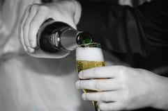 En un vidrio vierta el champán Fotos de archivo libres de regalías