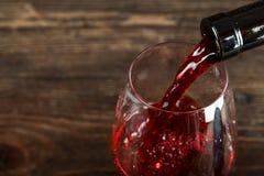 En un vidrio vierta el vino rojo foto de archivo libre de regalías