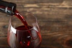 En un vidrio vierta el vino rojo imágenes de archivo libres de regalías