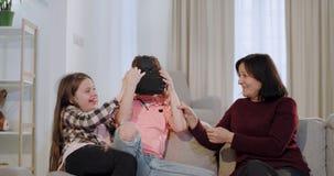 En una abuela de la sala de estar con sus nietos tenga un nieto del tiempo de la diversión que usa los vidrios de una realidad v