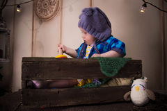 En una caja de madera un pequeño niño con un búho Imagen de archivo libre de regalías