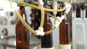 En una cervecería, una máquina llena las botellas de cerveza Un maquinista en el fondo controla el proceso Primer metrajes