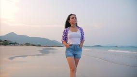 En una escena hermosa de la playa tropical de una mujer que camina en la playa del océano en la puesta del sol Primer del europeo almacen de metraje de vídeo