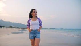 En una escena hermosa de la playa tropical de una mujer que camina en la playa del océano en la puesta del sol Primer del europeo almacen de video