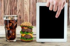 En una hamburguesa de madera de la tabla, cola con la preocupación del hielo y de la tableta del blanco Imágenes de archivo libres de regalías