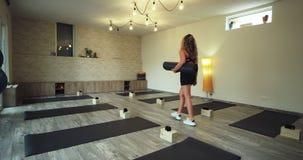 En una mujer moderna del estudio de la yoga de la salud que la camina con una estera del deporte a través del estudio que viene t almacen de metraje de vídeo