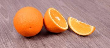 En una naranja de madera del fondo, mitad de una naranja y una rebanada fotografía de archivo