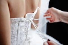 En una parte posterior del lazo de la novia un vestido de boda Imagen de archivo libre de regalías