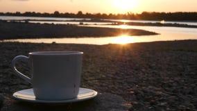 En una piedra fría por el río, hay una taza blanca de té o de café caliente Primer a cámara lenta, 1920x1080, hd almacen de metraje de vídeo