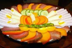 En una placa de pedazos cortados de carne y de verduras Imagenes de archivo