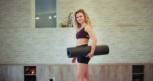 En una señora apuesta del estudio aerobio moderno con un cuerpo apto que la mira derecho a la cámara carismática que sostiene a metrajes