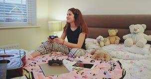 En una señora joven del dormitorio lindo del adolescente que juega en un juego de Playstation ella es muy concentrada y sonriente almacen de metraje de vídeo
