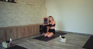 En una señora natural hermosa de la estera del deporte lista por un tiempo de la meditación de la yoga en un estudio de la yoga e metrajes