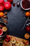 En una superficie una cacerola con el vino reflexionado sobre, un tablero con la manzana corta, los arándanos, las naranjas, y la Foto de archivo