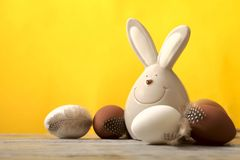 En una superficie de madera hay un conejo alegre y huevos marrones y blancos, un fondo amarillo de pascua foto de archivo