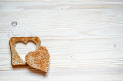 En una superficie de madera miente la tostada con la supresión en su corazón El top en tostada es un corazón del grano Fotografía de archivo libre de regalías