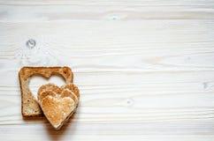 En una superficie de madera miente la tostada con la supresión en su corazón Top en mentira de los corazones del pan de la tostad Imagen de archivo
