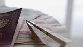 En una tabla blanca hay mucho dinero, un pasaporte y un peque?o aeroplano hechos del dinero El concepto de resto metrajes