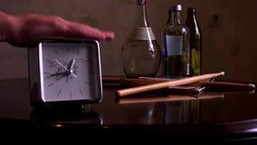 En una tabla de madera marrón pulida, con una reflexión, hay plata cuadrada con un dial blanco, un reloj y palillos del tambor metrajes