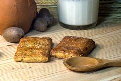 En una tabla de madera puesta una cuchara de madera con la miel y soporte al lado de un vidrio de la leche y de un pote de arcill Foto de archivo
