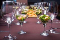 En una tabla en el restaurante hay vidrios y ensalada Fotos de archivo