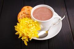 En una tabla a la taza de café con leche, algunas galletas de harina de avena y la flor amarilla dentro Imagen de archivo