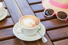 En una tabla marrón de madera es una taza con capuchino, un sombrero, vidrios Verano, café, resto Foto de archivo