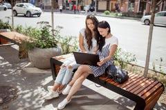 En una tarde soleada, dos señoras bonitas jovenes con el pelo oscuro largo, slothes casuales que llevan, se sientan en el banco a imagen de archivo libre de regalías