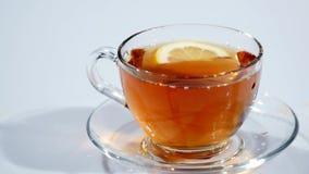 En una taza en un platillo con té negro cae una rebanada del limón en un fondo blanco, MES lento almacen de metraje de vídeo