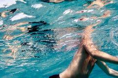 En undervattens- simning för manlig kropp i ett klart blått hav och framsidan Royaltyfri Bild