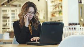 En ung affärskvinna arbetar i ett kafé och svarar en påringning flicka i affärsdräkten som arbetar på bärbara datorn lager videofilmer