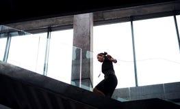 En ung affärskvinna som i regeringsställning som går upp trappan bygger royaltyfri foto