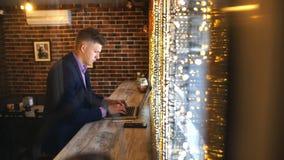 En ung affärsman arbetar i ett kafé med en bärbar dator arkivfilmer