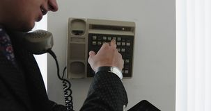 En ung affärsman i en dräkt använder en tappningtelefon för inre kommunikation i kontoret stock video