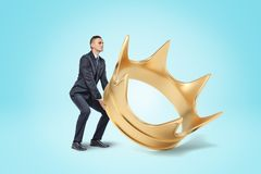 En ung affärsman i en smart dräkt som försöker att lyfta en enorm guld- krona från golvet royaltyfri bild