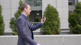 En ung affärsman kommer med trådlösa hörlurar i hans öron och lyckligt samtal på en video appell på smartphonen stock video