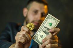 En ung affärsman rymmer ett mynt av bitcoite i hans hand royaltyfri bild