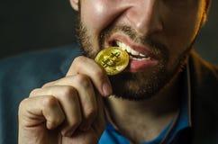 En ung affärsman rymmer ett mynt av bitcoite i hans hand royaltyfria bilder
