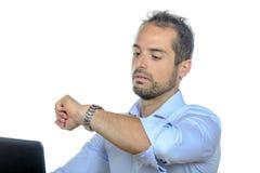 En ung affärsman som ser hans klocka Royaltyfri Foto