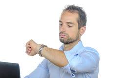 En ung affärsman som ser hans klocka Royaltyfri Bild