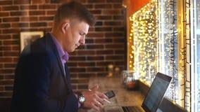 En ung affärsman som talar på telefonen och arbetet på en bärbar dator i ett kafé arkivfilmer